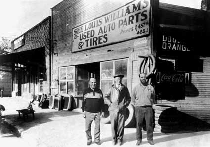 Louis, son, and grandson in front of 1932 storefront